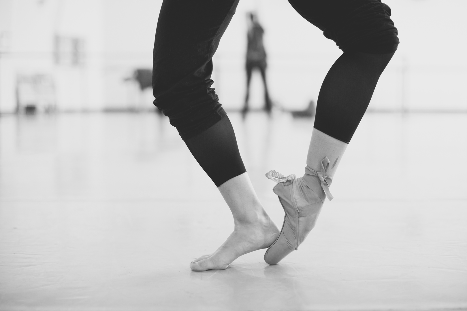 A ballerina practices on pointe